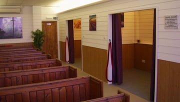 Brown & white funeral ceremony room with pews & smaller curtained funeral rooms off to the side