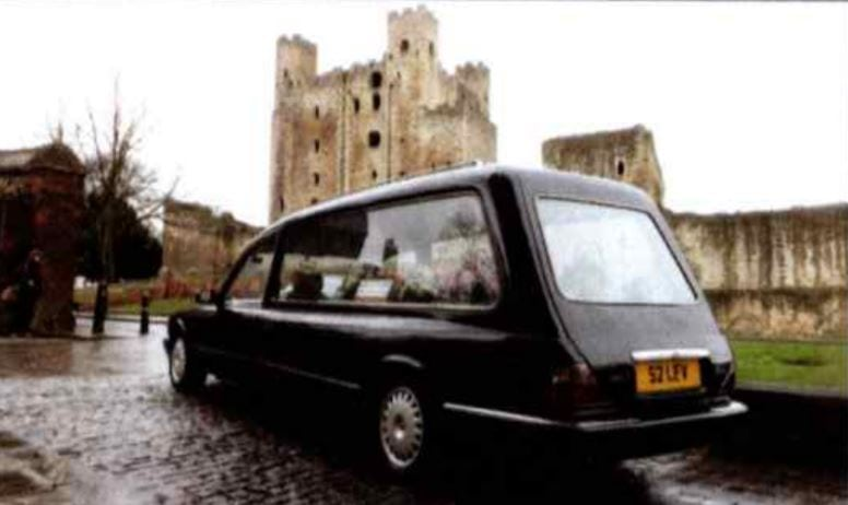 Rear view of black Daimler hearse with Rochester Castle in the background