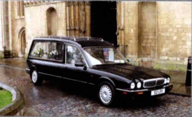 Black Daimler hearse parked outside a church