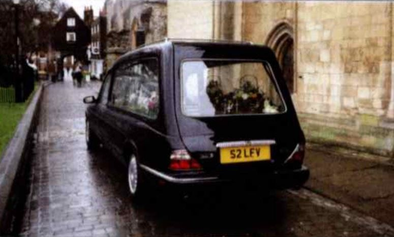 Rear view of black Daimler hearse parked outside a church
