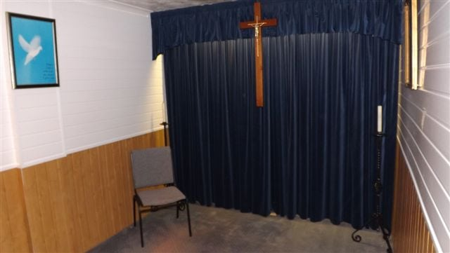 Brown & white funeral room with blue curtain & wooden cross