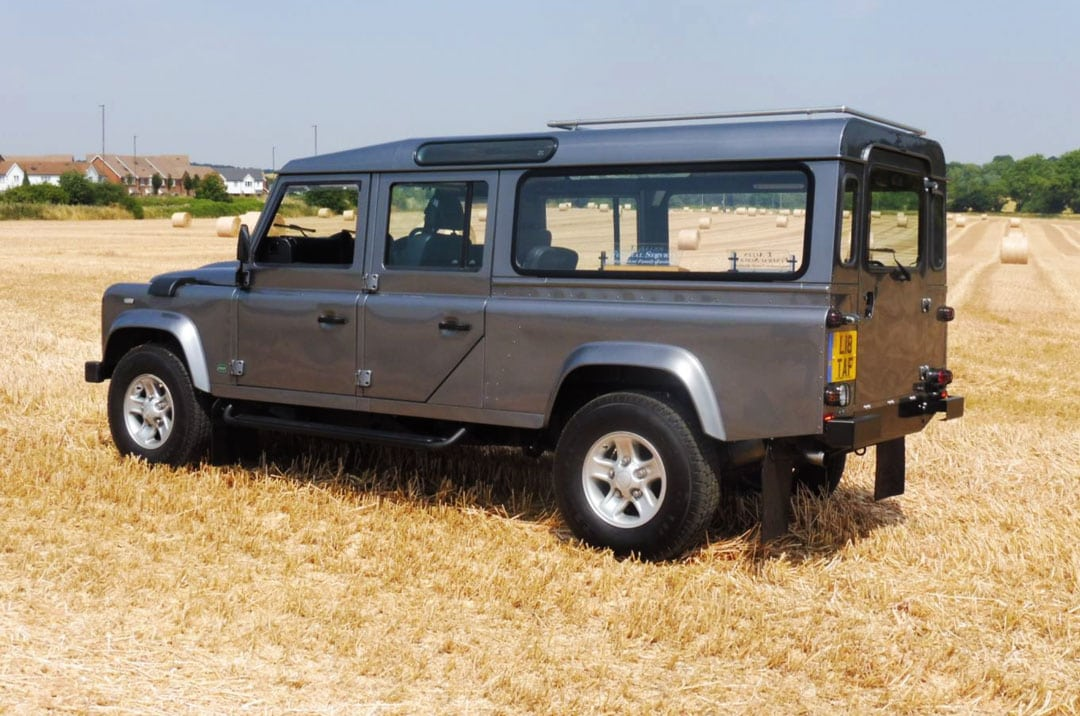 Side view of grey Land Rover Defender hearse in a recently cut crop field