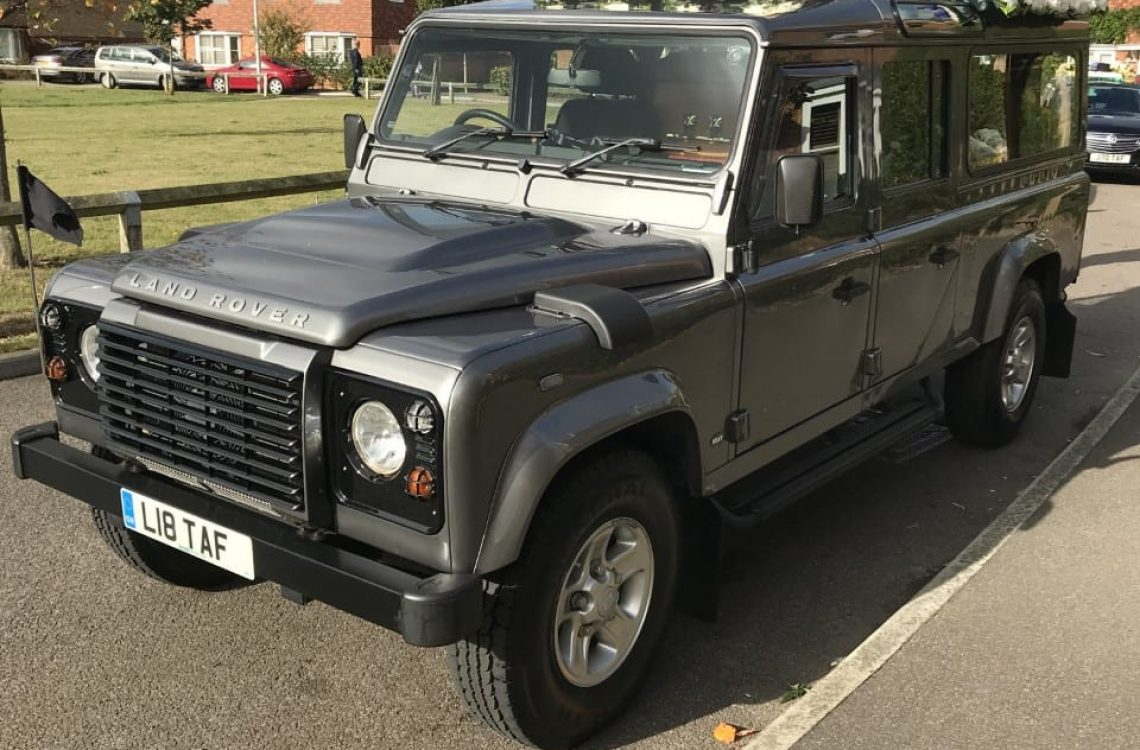 Grey Land Rover Defender hearse decorated with flowers ready for funeral ceremony